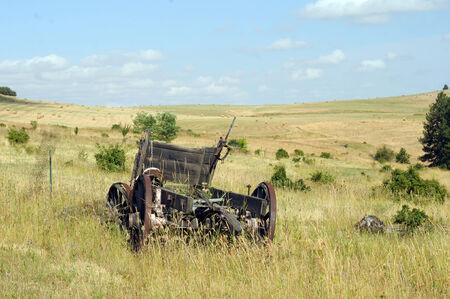 Old wooden wagon sitting atop grassland hill