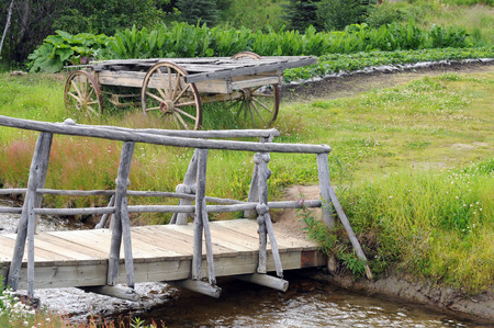 Old wooden walking bridge with wagon across stream
