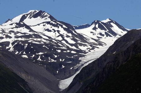 stark: Stark Alaskan glaciers point against blue skies Stock Photo