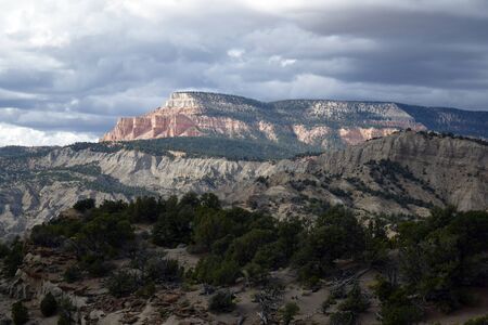 ピンク/オレンジ ビュート フォア グラウンドで別のグリーン ツリー覆われたビュートの灰色、荒れ模様の空に対して際立っています。 写真素材 - 66677756