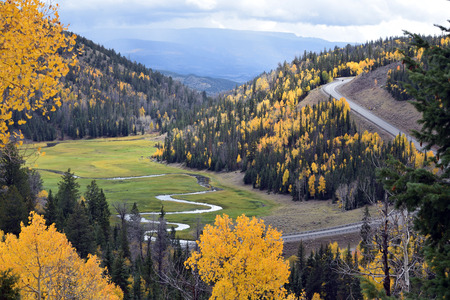 Curving  highway around river running through a meadow surrounded by gold autumn trees, and mountains circling a meadow.