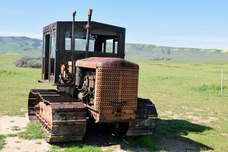 tred: Old farm tractor with steel tracks and wooden cabin with windows stands in open meadow.