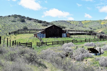 Old fenced barn stands in middle of grassland with hills  in background tinged with wildflowers against a blue sky.