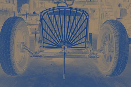 Blue-toned photo in shed of antique race carâ??s front grill with old-fashioned crankshaft on outside. 版權商用圖片