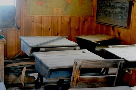 Antique wooden desks sit in abandoned school room with  faded old maps on walls. Stock Photo
