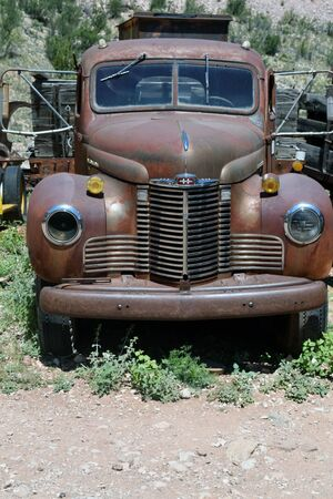 Antique rusted International Truck rests in weeds against a hill at a ghost town near Jerome, Arizona.