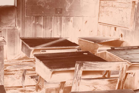 Copper-toned photo of the inside of an old deserted school room with wooden desks and maps on its walls.