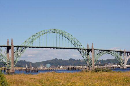 Yaquina Bay Bridge, an arch bridge, crosses an estuary fed by the Yaquina River near Newport, Oregon.