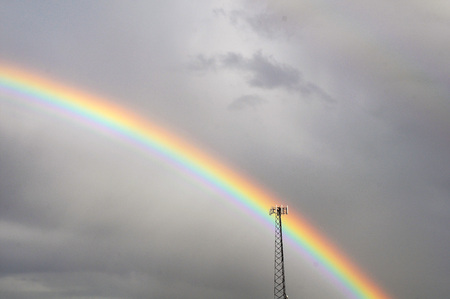 Early morning rainbow appears against darkened gray sky as background for lone cell tower