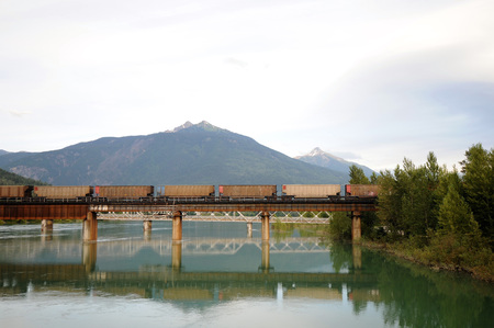 Train crossing railroad bridge at Revelstoke, Canada leaves reflection on the Columbia River below.