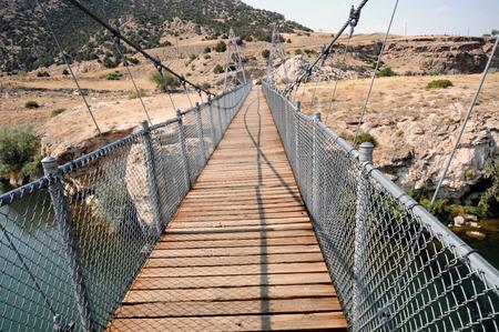 Swinging historic iron suspension bridge at Hot Springs State Park, Thermopolis, Wyoming, crosses Big Horn River.