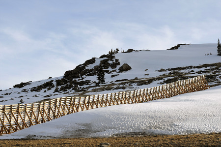 Wooden snow-drift fence runs up isolated hillside in the Big Horn Area, Montana Stock Photo