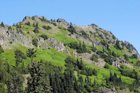 Washington graniet heuvel bedekt met diepe groene bomen en struiken tegen stevige blauwe luchten Stockfoto
