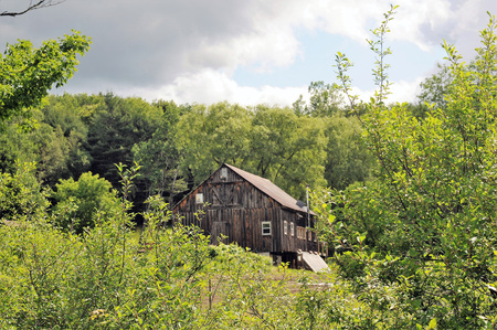 Oude doorstane grijze structuur in Vermont omringd door de lente groene bomen, shrubbery en gras. Stockfoto