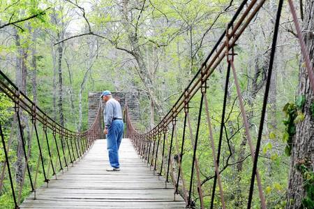 Man crossing aged Tishomingo stone and wood swinging bridge among greenery in dense forest.    Stock Photo