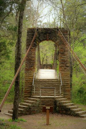 Sturdy timeworn Tishomingo stone and wood swinging bridge sits among greenery in dense forest. Stock Photo