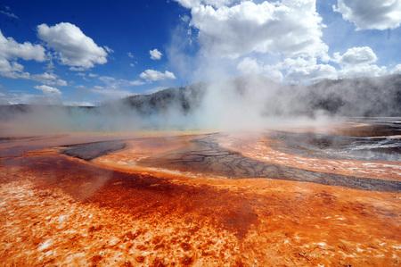 Helder gekleurde geothermische stoomopening in Nationaal Park Yellowstone tegen heldere blauwe hemel met witte wolken.