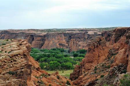 Kleurrijke outcroppings met groen en mesa tegen blauwe hemel bij Canyon de Chelly, Arizona.