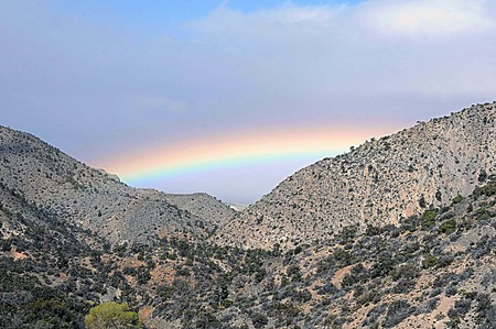 Pass between desert mountains frame a multicolored rainbow of blue, turquoise, purple and pink