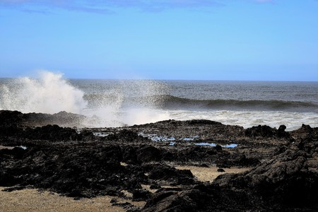 Kustgolven breken en plonsen op donkere rotsachtige outcrops tegen heldere blauwe Oregon lucht.