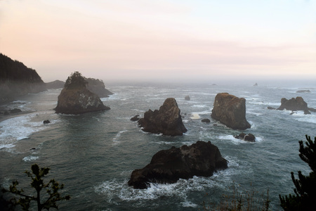 Hazy pinkish morning along the Oregon Coast with huge rock formations among ocean waves.