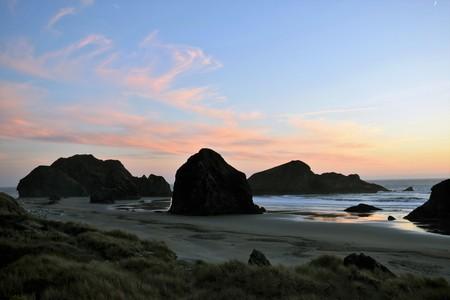 Roze wolk zonsondergang in blauwe lucht over rotsformaties en oceaan op de Oregon kust.