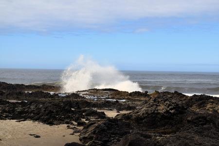 Wave crashes against dark rocky coast with blue sky over ocean on Oregon coast.