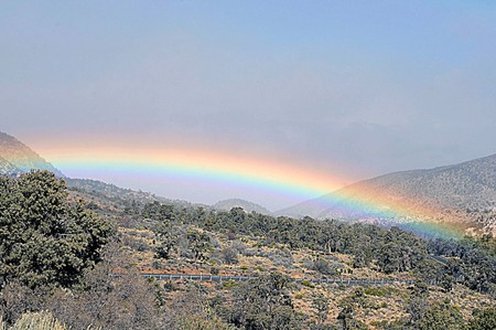 Multicolored rainbow arches over desert hillside with rural road winding around the scenic view Stock Photo