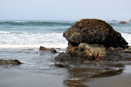 Dark barnacle encrusted boulder fronts blue ocean foaming waves on Oregon's southern coastal region.