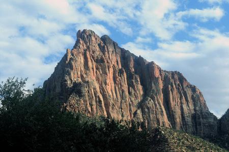 Een van Utah's kleurrijke formaties toont zijn kleuren tegen een blauwe witte wolkhemel.