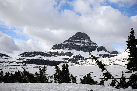 Besneeuwde berg en weide op Going to the Sun Road in Glacier National Park.