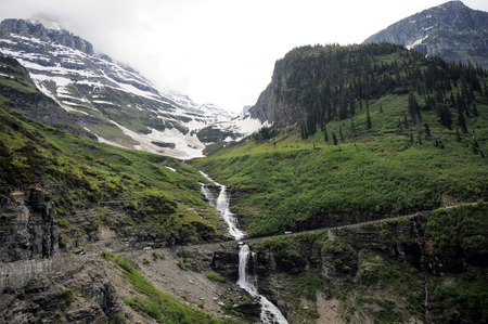 Waterfall trickles down mountain on Going to the Sun Road at Galcier National Park.