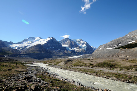 Gray glacial fed river flows from icy mountains along Canadas Icefield Parkway Stock Photo