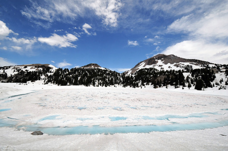 Melting ice covered lake shows crack of  blue water at Lassen Volcanic National Park.