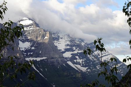 Wolken zweven over bergen in Montana's Glacier National Park met groene gebladerte op de voorgrond.