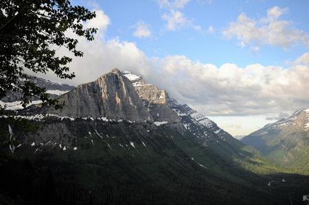 De heldere blauwe en witte bewolkte hemel hangt over de sneeuwbergen van Montana met groen bos.