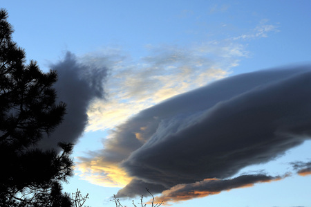 Dark blustry cloud, shaped like a torpedo, looms against blue sky and sunlit vapors.