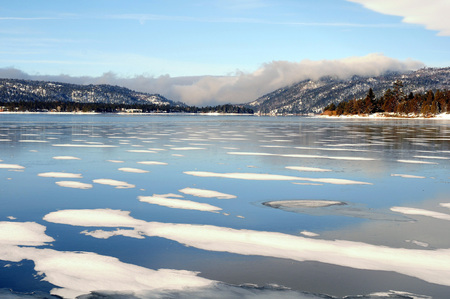 Splotchy ice and snow covered lake with mountains and blue skies in background.