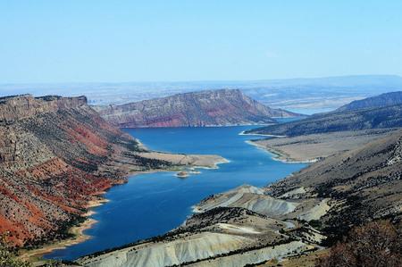 Vlammend kloofreservoir raakt Utah en Wyoming, omringd door kleurrijke zandstenen en kwartsietheuvels.