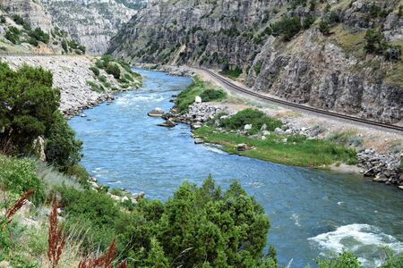 The Beauteous Wind River, Wyoming, Travels through Steep Canyon Walls by a Winding Railroad Track 写真素材 - 132049268