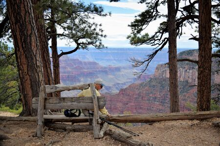 Hiking man rests on rustic wooden bench overlooking North Rim of Grand Canyon, Arizona.