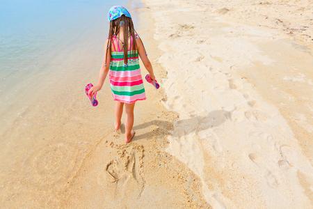 Adorable little girl walking alone white sand Caribbean beach