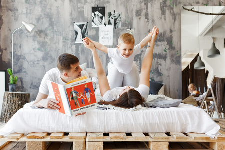 Happy family playing together on the bed in the room. Mom, Dad and little son in white clothes on the bed. Family relationship concept. Stockfoto