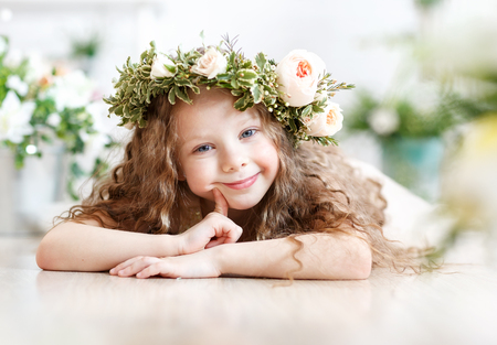 Kid in a flower crown. Cute little girl in a bright studio sits and looks into the camera