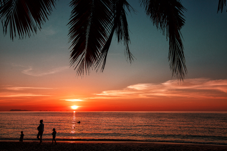 Silhouette of a family on the background of the setting sun on a summer day in the tropics. A picture of a gorgeous orange sunset in Asia