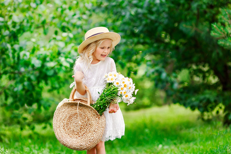 Portrait of cute little girl in a park on a picnic with straw basket and hat. Spring sunny concept. Happy mothers day. Little girl attacked by mosquitoes.