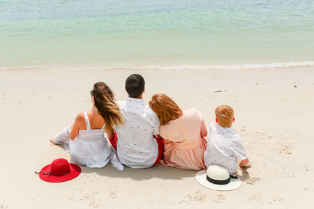 Back view of a happy family of four are sitting on tropical beach. A poster.