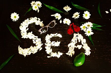 Table top view image of item for summer holiday background concept. Flat lay beach table and sun glasses with item of vacation season. The word sea of white flower petals on a black table.