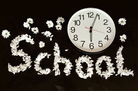 Flatlay big clock on a black background and the word school made of white petals. Concept back to school. Banque d'images - 132049712