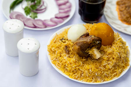 Delicious spicy chicken rice in white plate on white background, Indian or Pakistani food.